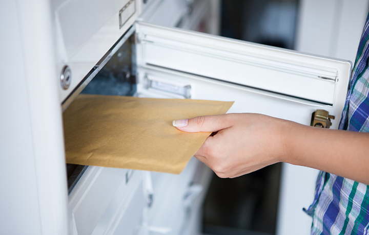 женска€ рука достает конверт из почтового €щика